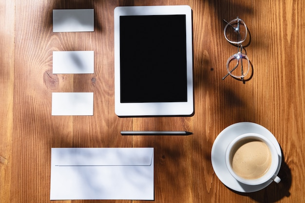 Gadgets, coffee, work tools on a wooden table indoors.