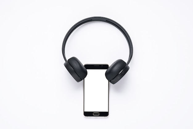 Gadgets for music lovers, smartphone with white screen with wireless headphones.