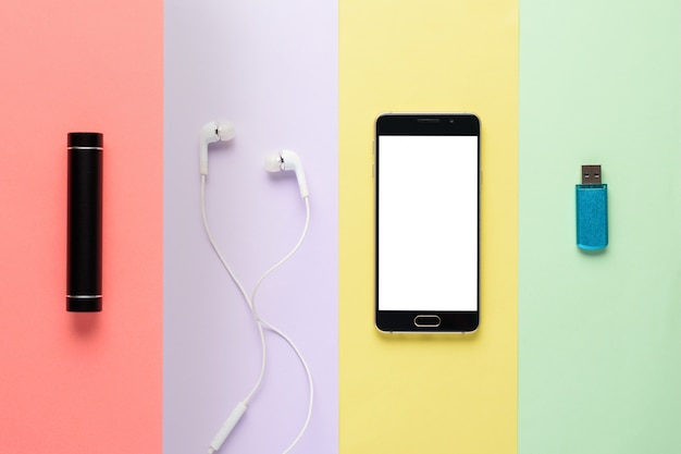 Gadgets. smartphone, power bank, headphones, flash drive on multi-colored striped