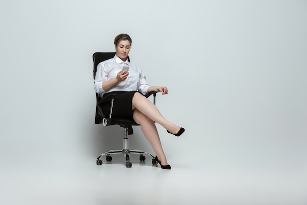 Gadgets. young woman in office attire. body positive female character, feminism, loving herself, beauty concept. plus size businesswoman on gray wall. boss, beautiful. inclusion, diversity.