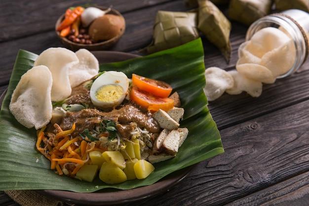 Гадо-гадо. традиционная индонезийская кухня. рисовый пирог, яйцо и овощи с арахисовым соусом