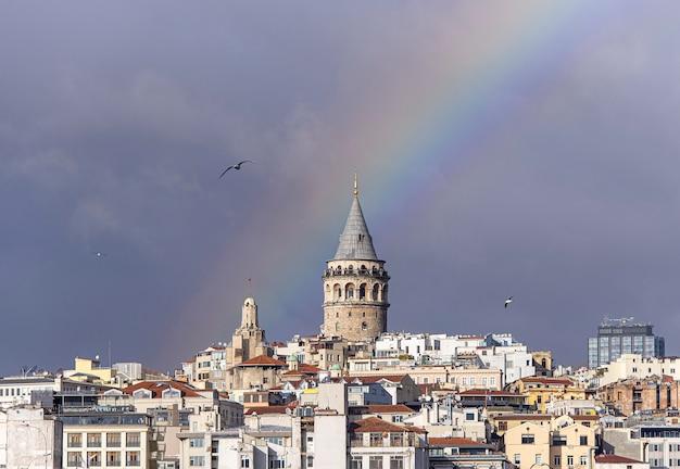Галатская башня или галата кулеси в стамбуле после дождя с радугой на небе, турция