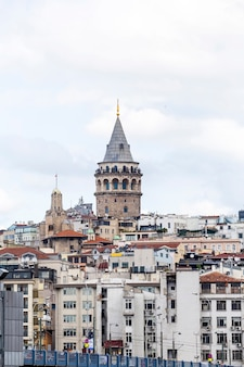 Galata tower visible above the rows of residential buildings at cloudy weather, istanbul, turkey
