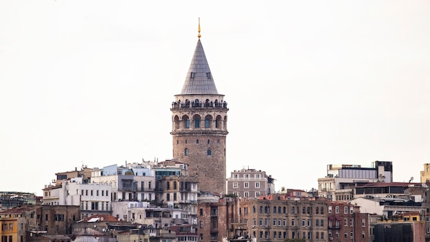 Galata tower with levels of residential buildings in front of it at cloudy weather istanbul, turkey