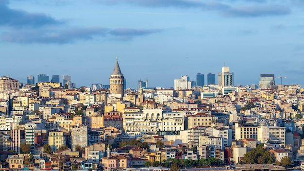 Galata tower with levels of residential buildings in front of it and modern buildings at cloudy weather istanbul, turkey