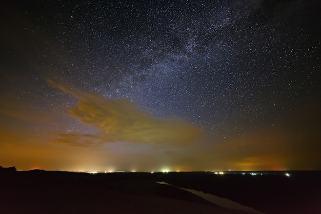Galaxy milky way with clouds in the night sky against the background of the river