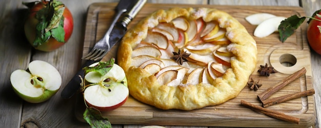 Galette with fresh apples on a wooden cutting board