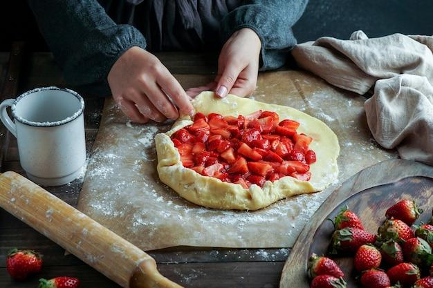 準備の新鮮なイチゴのプロセス、若い女性の手、生地で作業するガレット