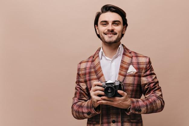 格子縞のブレザーとスタイリッシュなシャツを着た勇敢な若いブルネットの髪の紳士がまっすぐに見え、カメラを持っています
