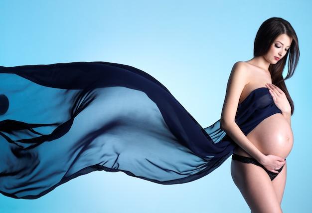 Galmour e stile di giovane donna incinta con materiale blu su blu