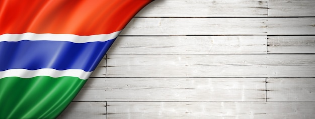 Gambia flag on old white wall. horizontal panoramic banner.