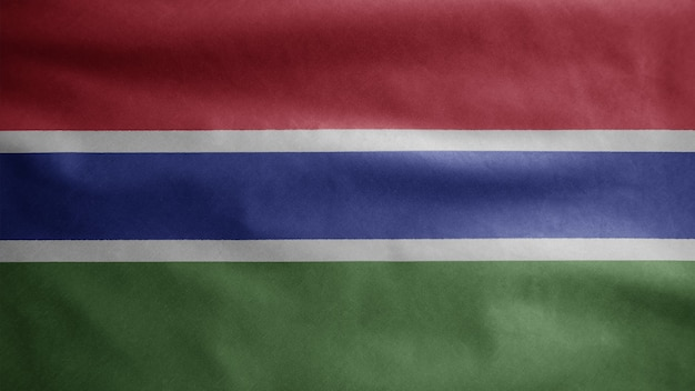 Gambian flag waving in the wind. close up of gambia banner blowing, soft and smooth silk. cloth fabric texture ensign background.