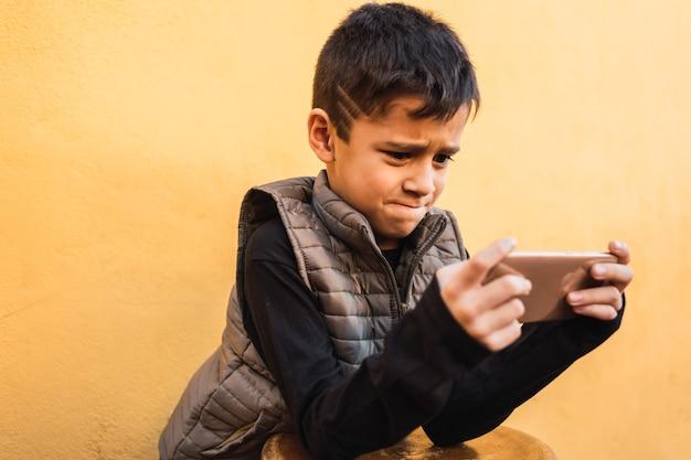 Зависимость от азартных игр - ребенок увлечен видеоиграми на мобильном телефоне.