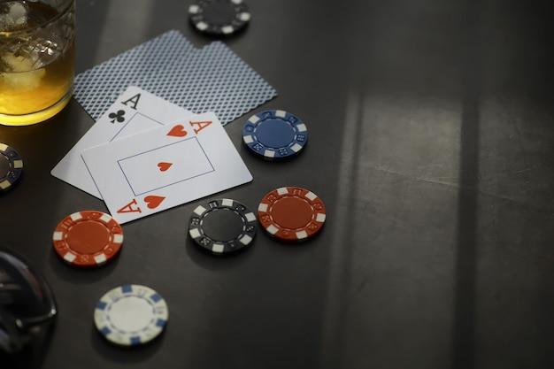 Азартные игры карточные игры на деньги. техасский холдем-покер. карты в руке, игральные фишки, колода карт с алкоголем в стакане.