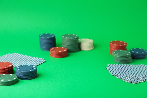 Gambling chips and card for poker on green wall. top view