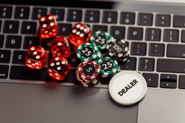 Gambling chips and dices on laptop keyboard