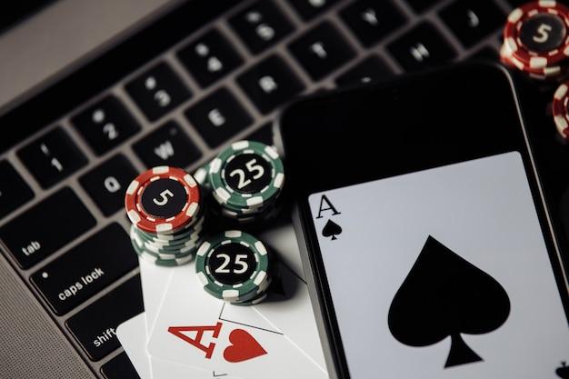 ギャンブルチップスマートフォンとキーボード上のトランプクローズアップオンラインカジノの概念