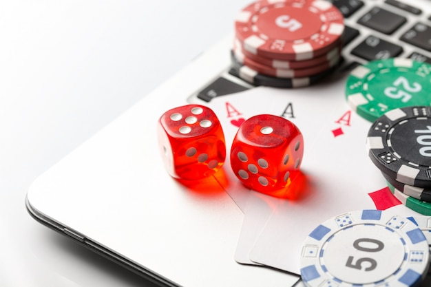 Gambling chips with dice and playing cards on laptop.