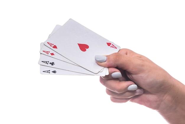 Концепция азартных игр. женская рука, держащая комбинацию из четырех тузов, изолированных на белом