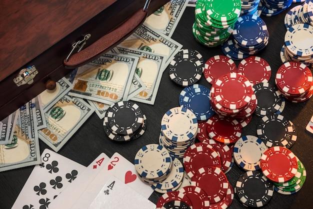 ギャンブルの概念。賭けは投資家にとっての賭けです。黒い壁にチップ、ドル、トランプがいっぱい入ったケース