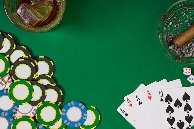ギャンブル、幸運、エンターテインメントのコンセプト-緑のテーブルの表面にカジノチップ、ウイスキーグラス、トランプ、葉巻をクローズアップ。上面図。静物