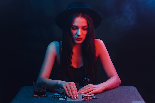 모자와 드레스를 입고 도박을 하는 소녀는 카지노에서 카드, 칩, 내기를 가진 테이블에서 포커를 합니다