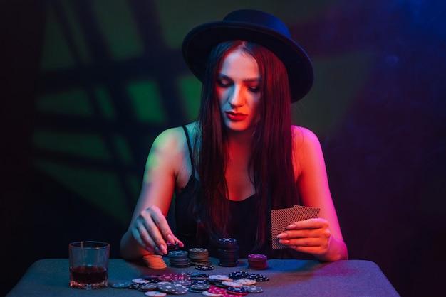 모자에 도박 소녀는 붉은 빛과 어두운 배경 카드와 함께 테이블에서 포커를 재생
