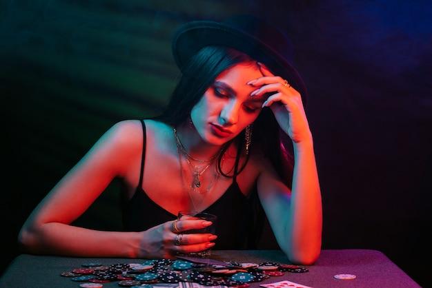帽子をかぶったギャンブルの女の子は、赤いライトと暗い背景のカードでテーブルでポーカーを再生します