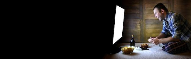 Азартный человек играет на консоли на джойстике перед большим экраном телевизора и длинным черным баннером для текста