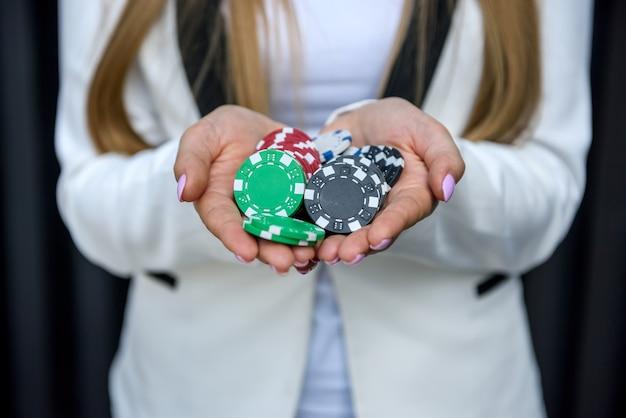 도박 테마. 다채로운 재생 칩 여성 손 클로즈업. 게임 초대