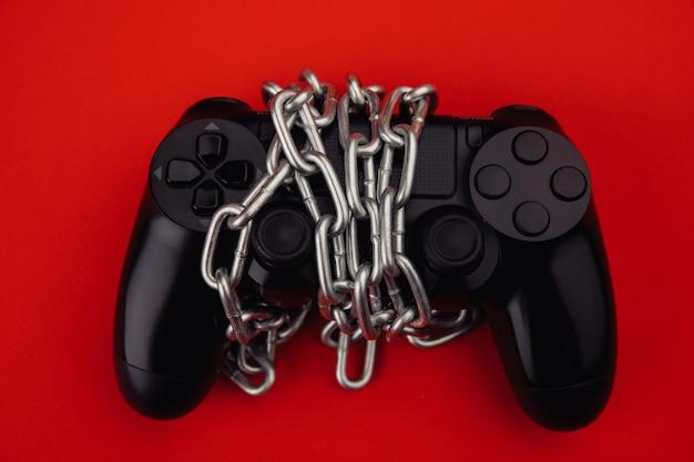 ゲーム中毒のコンセプト。ゲームパッドは鎖で結ばれています。