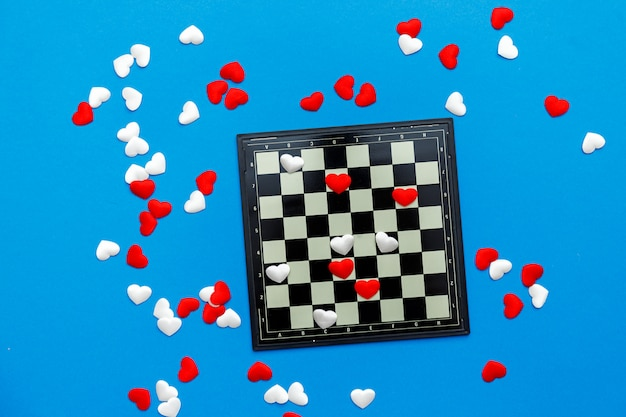 Game of checkers with red and white hearts on blue