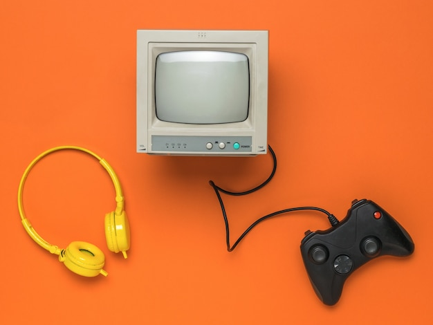 A game console, headphones and a gray monitor on an orange background.
