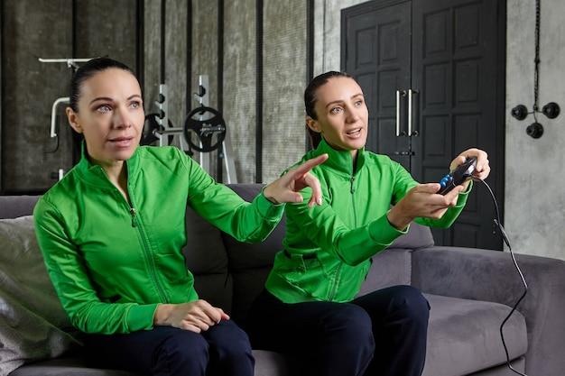 그녀의 여동생 옆에 있는 로프트 아파트의 소파에 앉아 있는 열정적인 여성의 손에 있는 게임 콘솔과