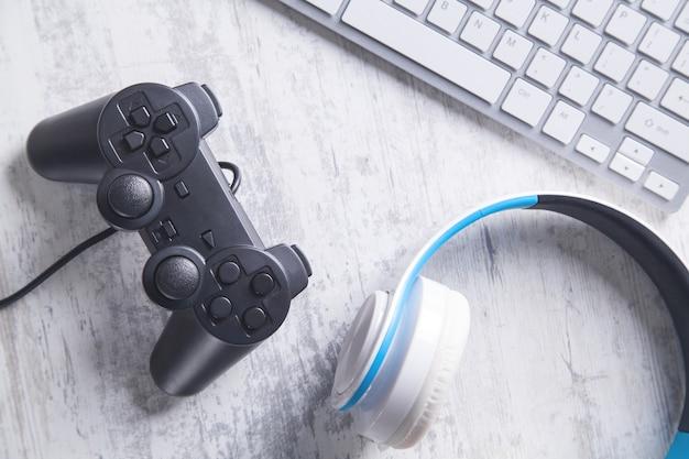 ヘッドフォンとコンピューターのキーボードを備えたゲームコントローラー。