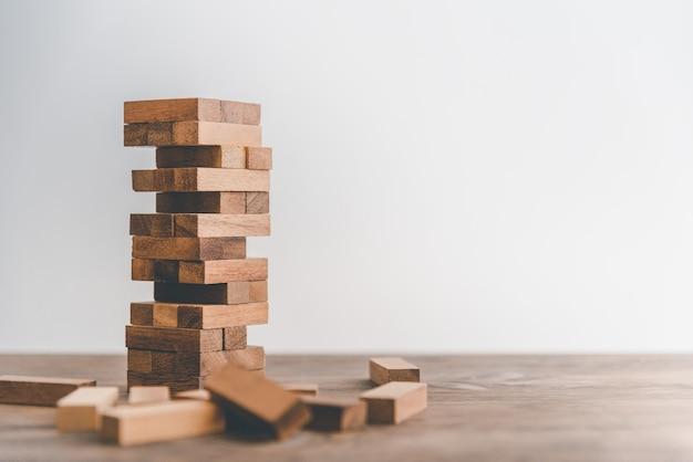게임은 타워에서 나무 블록으로 그려졌습니다. 비즈니스의 비즈니스 위험 개념. 계획 명상이 필요하며 사업상의 위험을 줄이기 위해 신중하게 결정해야합니다.