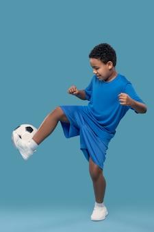 게임, 축구. 밝은 파란색 배경에 축구 공으로 움직이는 파란색 운동복에 어두운 피부 긴장된 소년