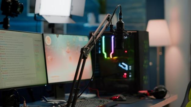 Rgb 전문 고성능 컴퓨터의 디스플레이에서 게임이 종료되고 가상 토너먼트를 위한 스트림 채팅이 준비됩니다. 네온 불빛이 있는 빈 게임 홈 스튜디오에서 전문 마이크를 스트리밍합니다.
