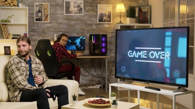 Игра окончена для молодых, играющих в видеоигры с гарнитурой vr, сидя на диване. подруга смотрит на парня после проигрыша в видеоиграх.