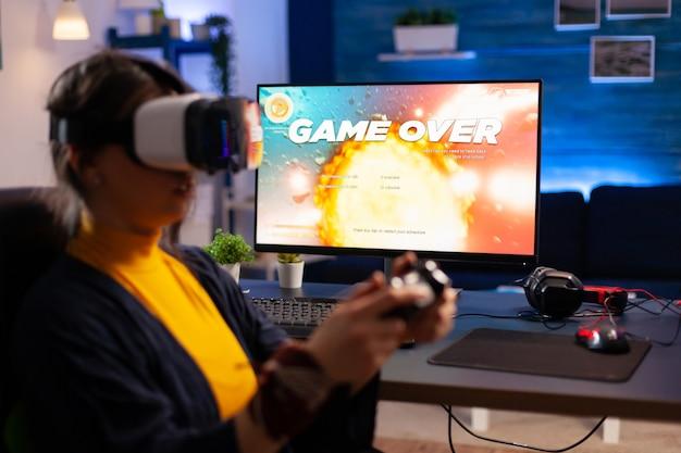 プロのvrヘッドフォンを使用してスペースシューティングゲームをプレイするサイバーゲーマーのためのゲームオーバー。リビングルームで夜遅くにゲーミングチェアに座ってオンラインチャンピオンシップのためにジョイスティックを使用して敗北したプレーヤー