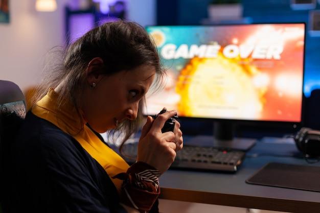 自宅のゲームスタジオで夜間に強力なコンピューターでビデオゲームをプレイするゲーマーのためのゲームオーバー。ネオンライトのある部屋でeスポーツトーナメントのオンラインビデオゲームをストリーミングする女性