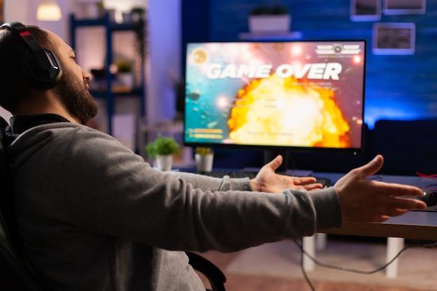 ゲーマーが自宅のゲームルームで夜間にコンピューターでビデオゲームをプレイするためのゲームオーバー。トーナメントを通じてオンラインサイバーパフォーマンスをストリーミングするヘッドフォンで敗北した男