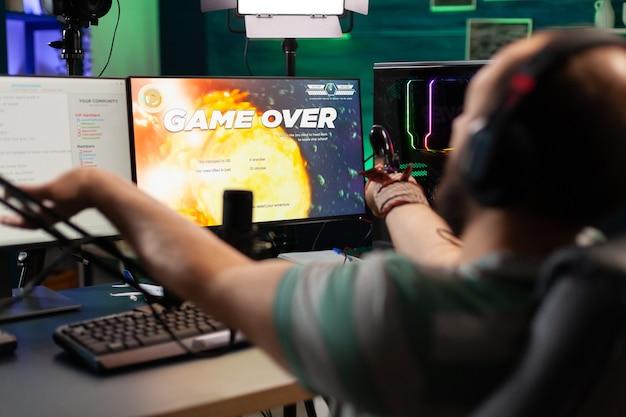 최신 헤드시트와 조이스틱을 사용하여 온라인 공간 사수 게임을 하는 남자 스트리머의 게임 오버. 전문 경쟁 중에 열린 채팅에서 플레이어와 대화하는 강력한 pc에서 사이버 수행