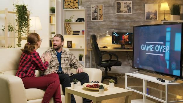 소파에 옆에 있는 그의 여자 친구와 무선 컨트롤러를 사용하여 비디오 게임을 하는 동안 남자를 위한 게임 오버.