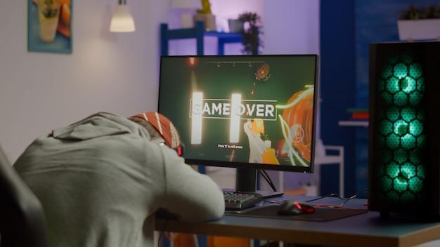 ゲームルームでrgbキーボードを使用して、強力なコンピューターでシューティングビデオゲームをプレイする悲しいゲーマーのためのゲームオーバー。オンライントーナメントを通じてオンラインサイバーパフォーマンスをストリーミングするヘッドフォンで敗北した男