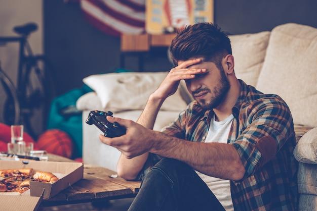 ゲームオーバー。ジョイスティックを保持し、額に手を置いて欲求不満の若い男