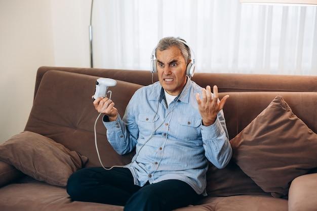게임 끝. 콘솔 제어 조이스틱을 사용하여 게임을 하는 중년 남자. 잠금 기간 동안의 엔터테인먼트. 게임을 졌습니다. 배경에 거실입니다. 플레이어는 화가 났고 화가 나서 조이스틱을 던졌습니다.