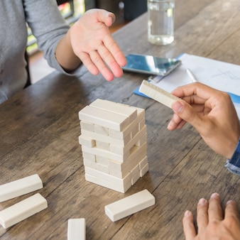 Game of physical and mental skill. keep balance. girl builds tower of wood blocks. entertainment activity. education, development. the girls collect a sprawling constriction of wooden blocks