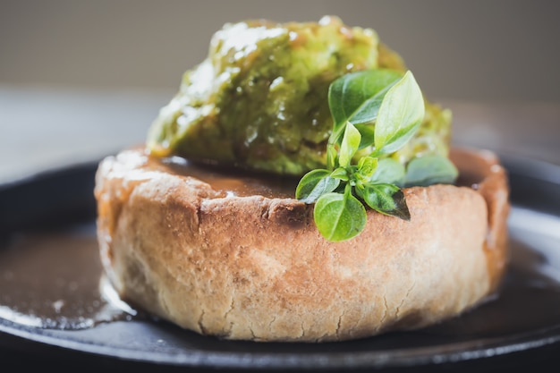 Game pie with duck meat in serving dish with peas puree and spinach leaves close up