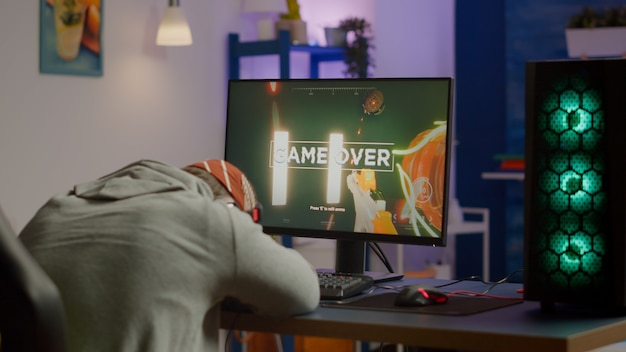 Game over per il giocatore triste che gioca ai videogiochi sparatutto su un potente computer utilizzando la tastiera rgb nella sala da gioco. uomo sconfitto con cuffie in streaming cyber online che si esibiscono attraverso un torneo online